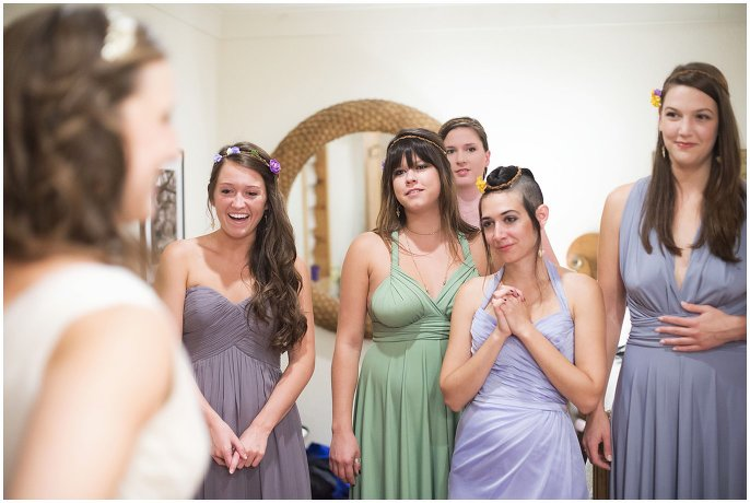 bride getting dressed with bridal party photo