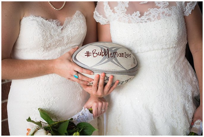 LGBT wedding with two brides and rugby ball photo