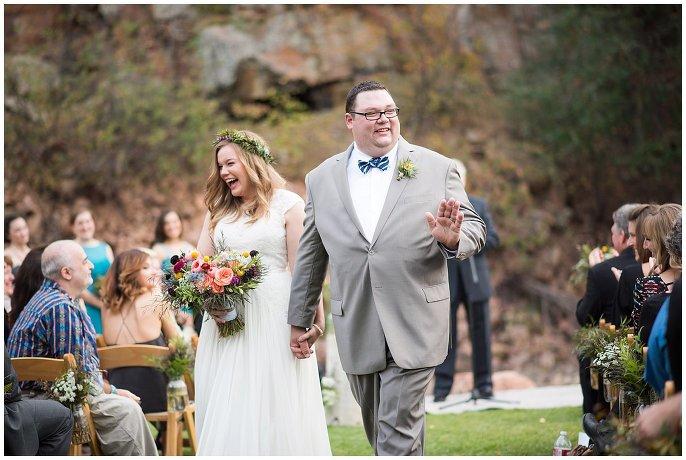couple walking down aisle boulder mountain wedding photo