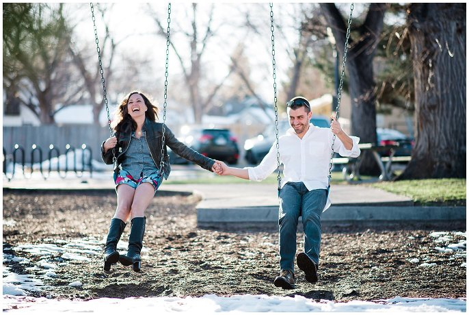 engaged couple playing on swingsets in small town colorado photo