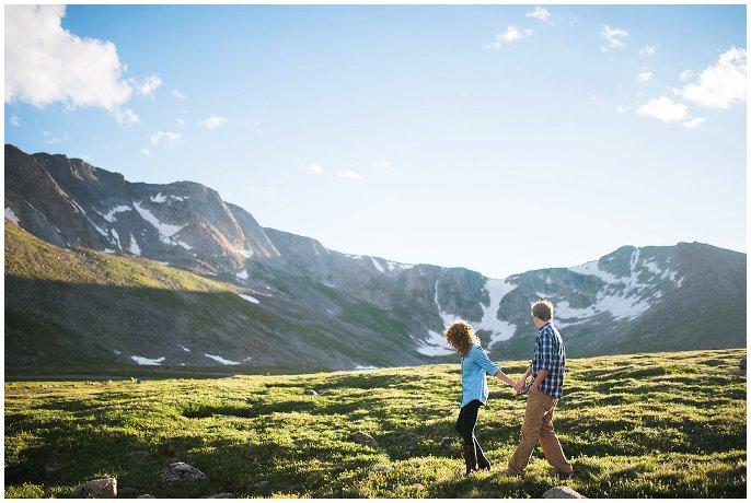 couple walking through fields in Colorado mountians
