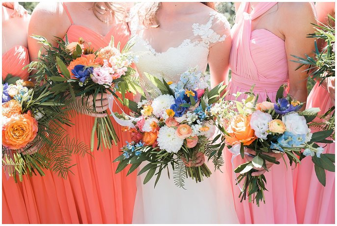 bridesmaids in mismatched coral dresses with mountain flowers photo