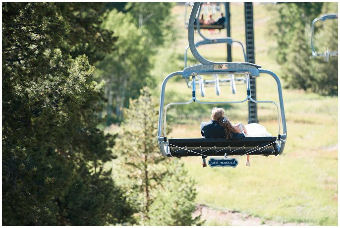 bride and groom riding chair lift down colorado mountain photo