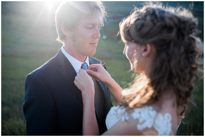 bride fixing grooms tie sunset mountain photo