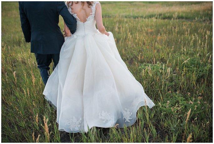 bride walking through field in custom lace wedding dress photo