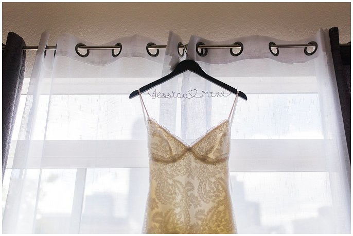 lace wedding dress hanging in window photo