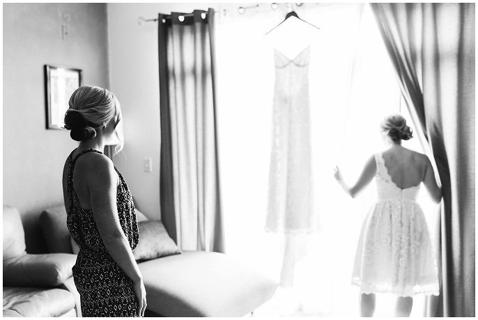 bride looking at lace wedding dress in window photo