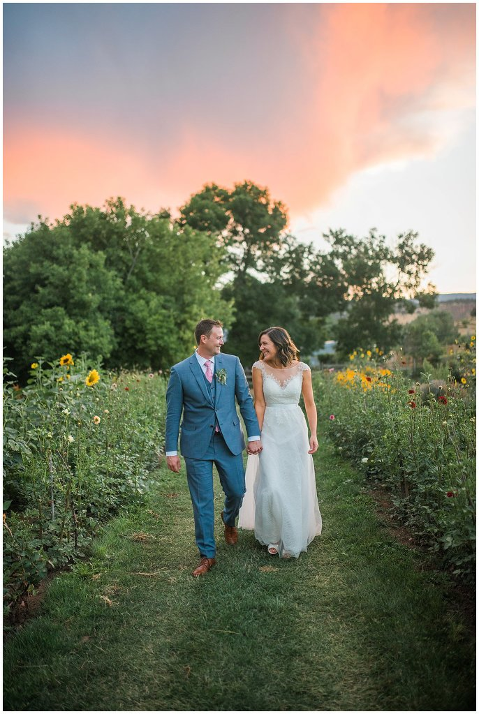 Bride and Groom walking in garden at sunset on wedding day photo