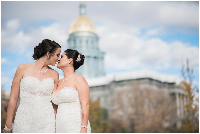 brides kissing in front of Denver capital photo