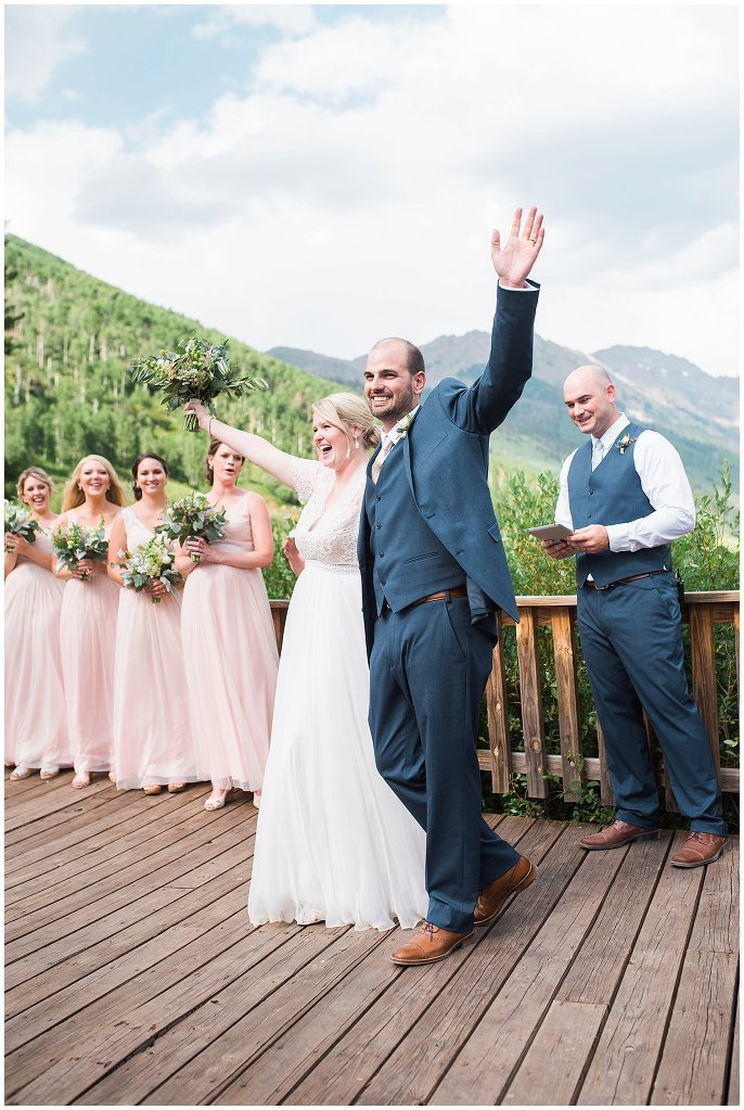 bride and groom cheering after wedding ceremony photo