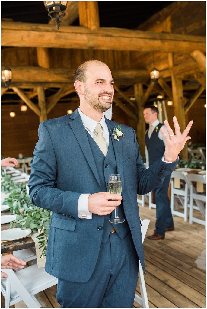groom in blue suit showing off wedding ring photo