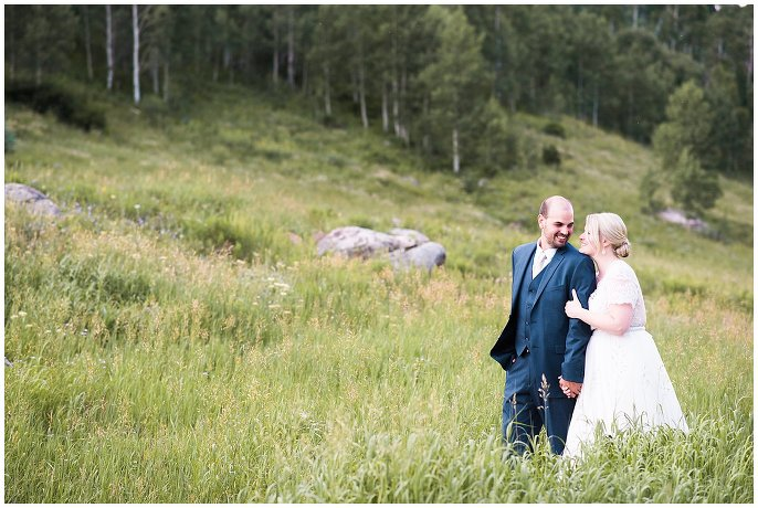bride and groom cuddling in the aspens on wedding day photo