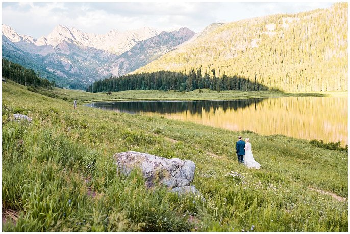 bride and groom walk by Colorado lake photo