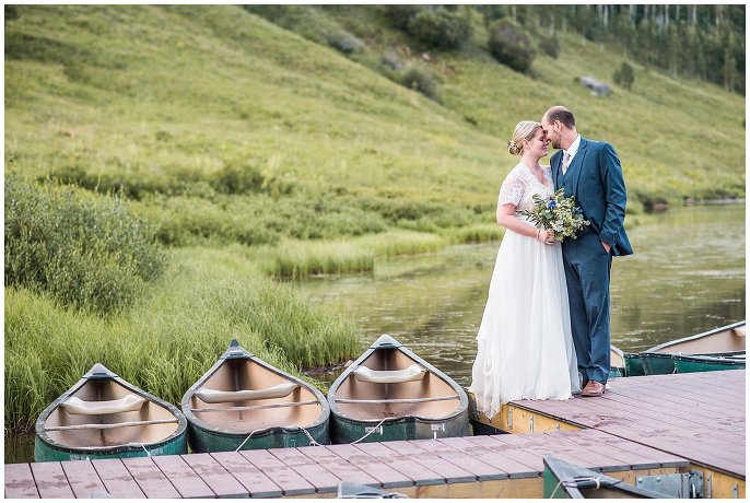 couple kissing on dock with canoes photo