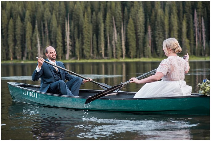 bride and groom rowing canoe on wedding day