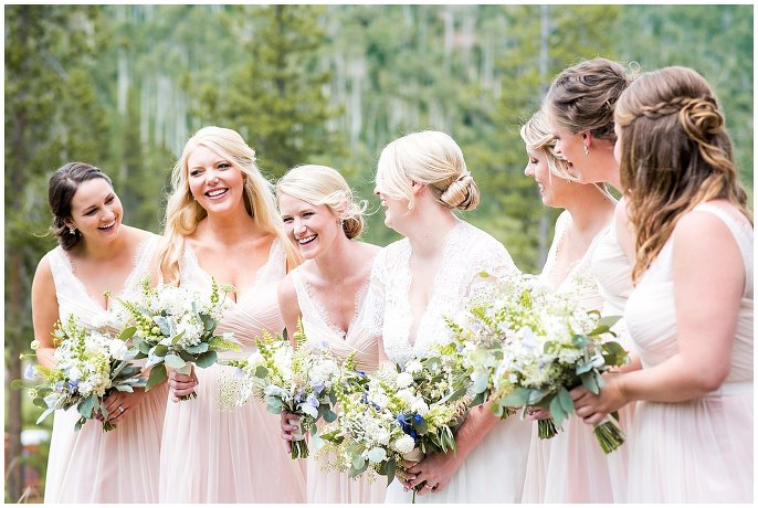 bride in lace dress and bridal party in pink photo