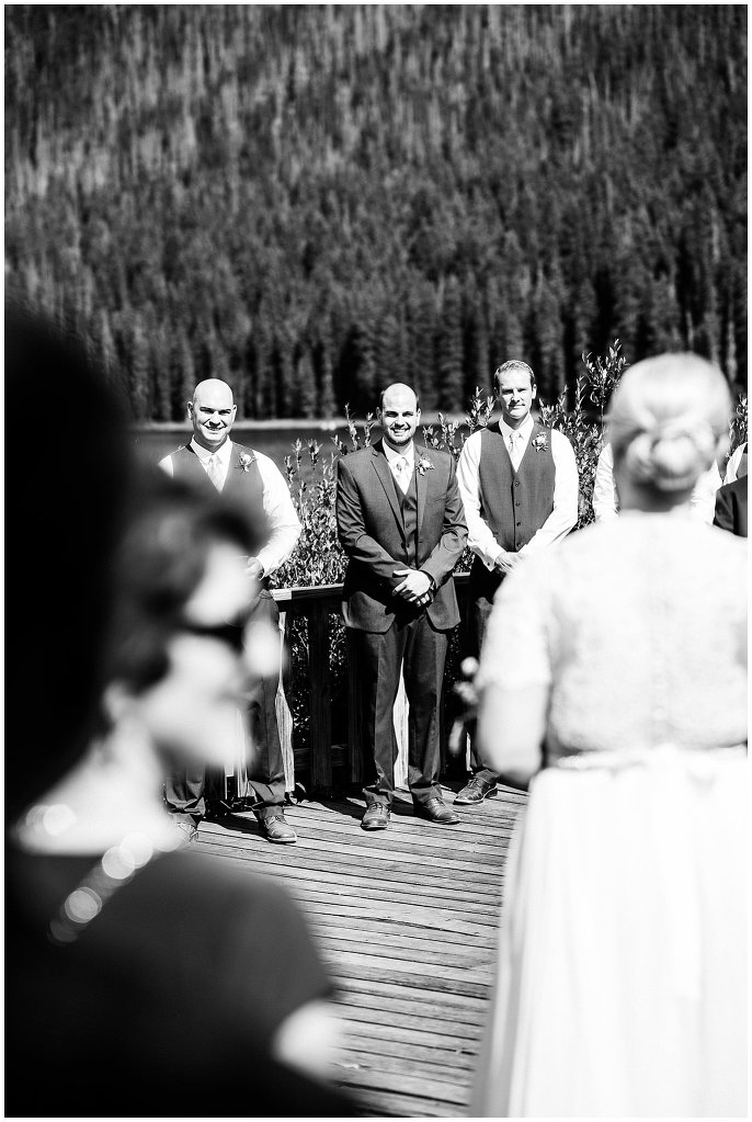 groom seeing bride as she walks down aisle photo