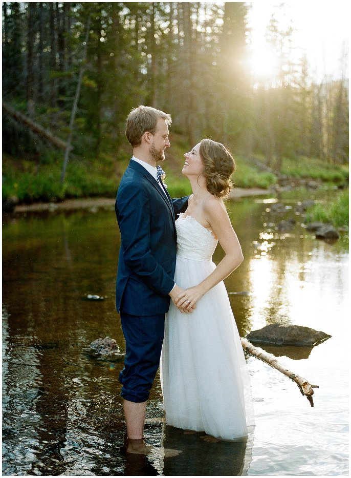 bride and groom wading in river photo