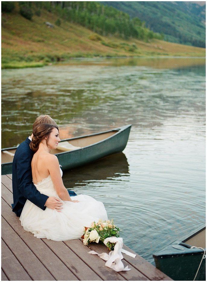 bride and groom with feet in lake photo