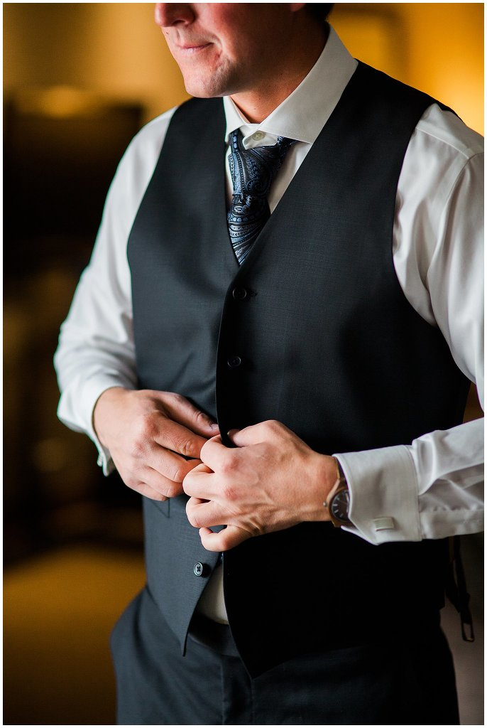 groom buttoning vest wedding day photo